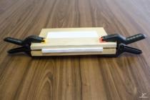 Balík sevřený mezi prkýnka svěrkami.